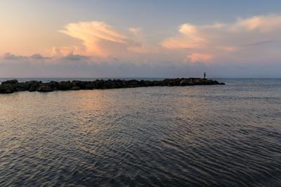 море, небо, камни и рыбак
