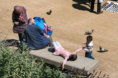 Семья на отдыхе. Парк в Барселоне Арабская семья дети голуби