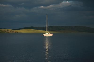 В луче солнца озеро яхта