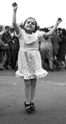 Полёт девочки на фоне веселящихся взрослых девочка полет танец детство ребенок платье улыбка прыгать летать