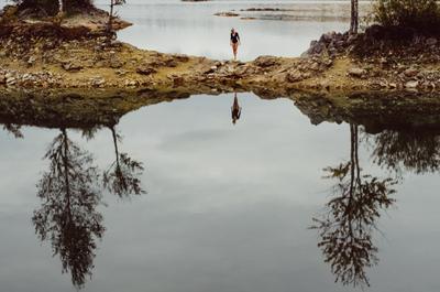 Перемычка девушка озеро карьер перемычка остров островок ноги боди деревья гладь отражение черный камни щебень вода зеркало кусты осень