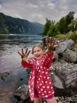 Замараю! Дети ребенок девочка в красной куртке красная курточка на берегу реки Енисея Енисее отдых грязные ручки у девочки руки грязи испачкались испачканные ребенка не повод для грусти весело отличное настроение устрашающий вид и цвет