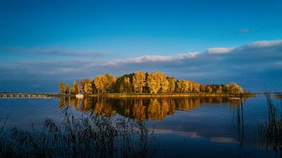 В лучах заходящего солнца вечер закат облака озеро остров отражение