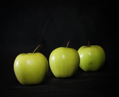 Три зелёных яблока на чёрном фоне яблоки