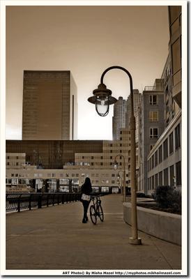 """Из серии """"Передача Света"""" США Америка вечер закат девушка велосипед фонарь солнце здание оффис дом набережная река причал Гудзон"""