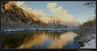 У озера Кавказ горы облака
