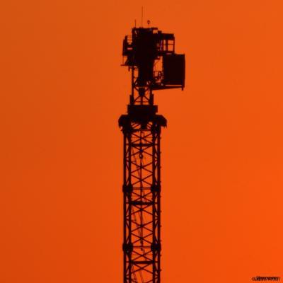 Эстетега индустриального минимализма - КранЪ - вид  сзади на закате оранжевый кран стройка стрела по ветру силуэт