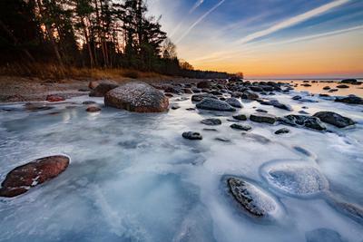 Замёрзший прибой море вода камни закат золотой час небо цвета лёд