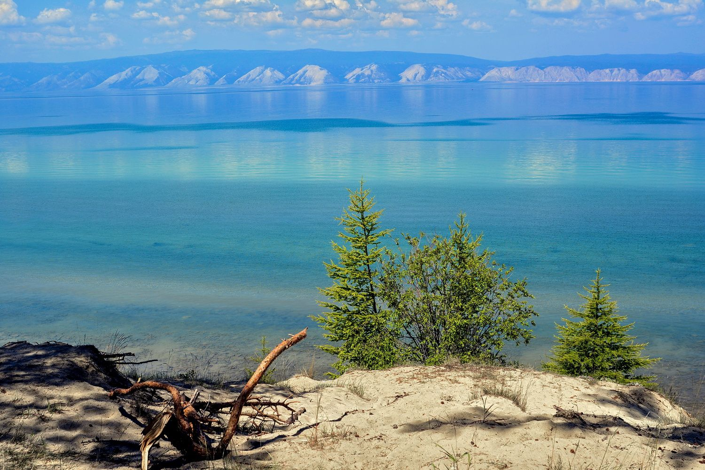 Кусочек берега Ольхона с видом на Прибайкальский хребет Байкал вода лето горы кустики жара