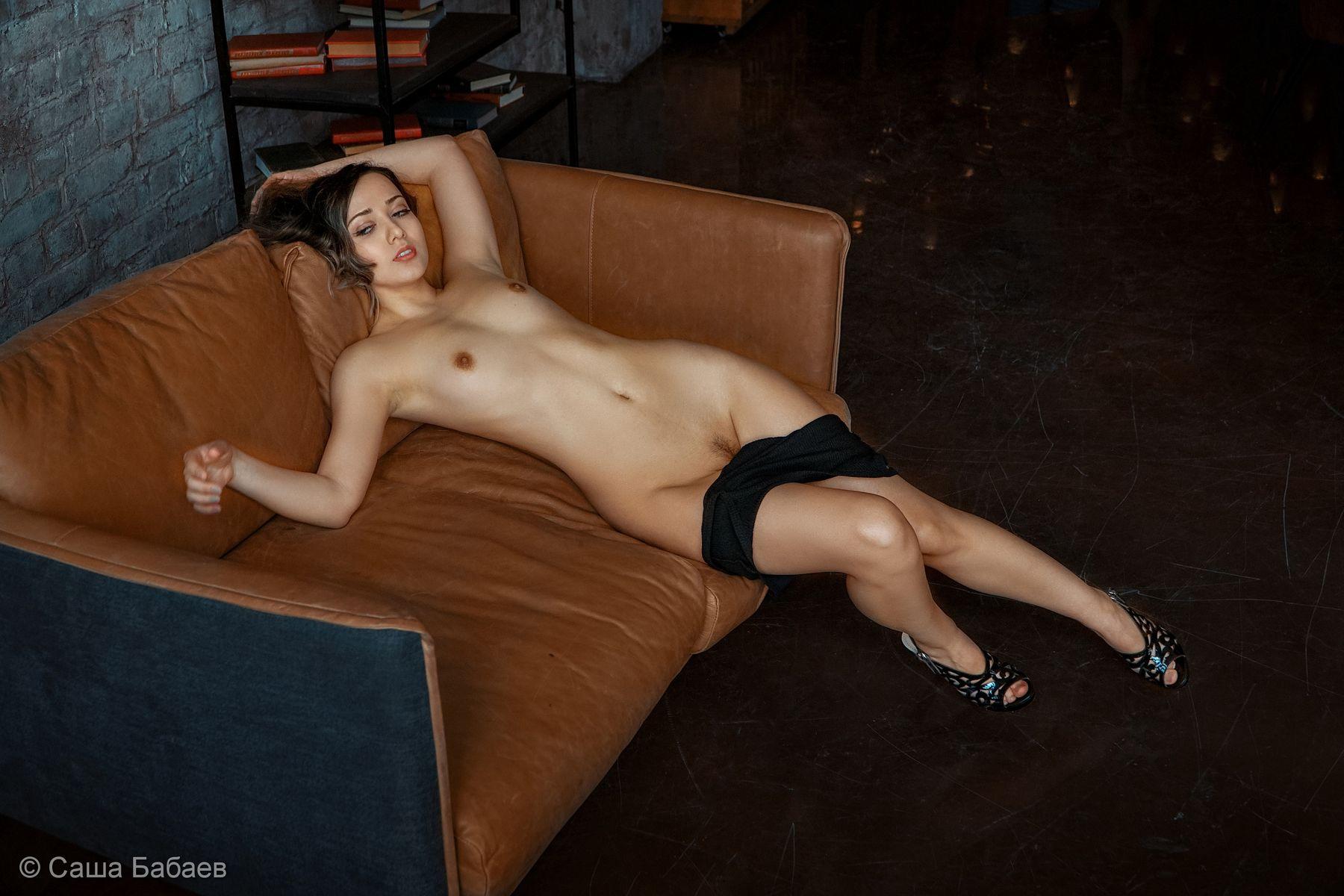 На диване.
