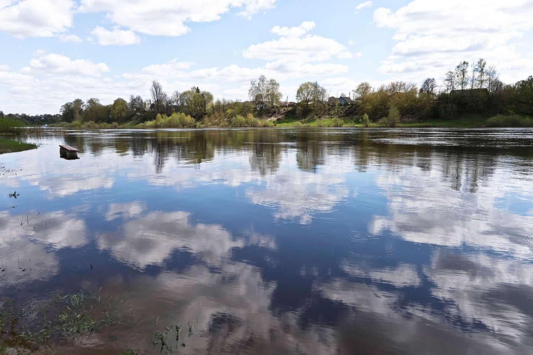 Белые облака отражаются в реке.