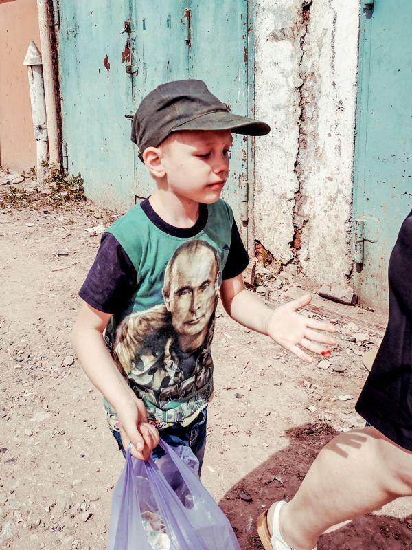 Из серии «Уличная экзистенция» Россия 2021 стрит фото улица люди фотограф наблюдения экзистенция город документальная репортаж мальчик Путин футболка палец кровь рана двор шагать день мода стиль одежда